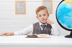 Niño divertido en escuela niño pequeño con el libro, educación de los niños foto de archivo