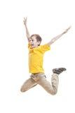 Niño divertido en la camiseta colorida que salta y que ríe Fotografía de archivo libre de regalías