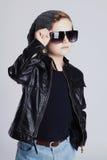 Niño divertido en sombrero Niño pequeño de moda en gafas de sol niño elegante en cuero Fotos de archivo