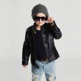 Niño divertido en sombrero Niño pequeño de moda en gafas de sol niño elegante en cuero Foto de archivo