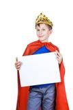 Niño divertido hermoso que finge ser un rey que lleva una corona y que sostiene la pequeña bandera en blanco Fotografía de archivo libre de regalías