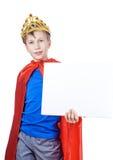 Niño divertido hermoso que finge ser un rey que lleva una corona y que sostiene la pequeña bandera en blanco Fotos de archivo libres de regalías