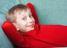 Niño divertido hermoso que lleva el suéter púrpura brillante que miente en una sonrisa del sofá Foto de archivo libre de regalías