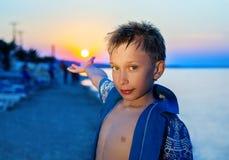 Niño divertido hermoso que se coloca en la playa en la puesta del sol el vacaciones de verano Foto de archivo libre de regalías