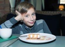 Niño divertido hermoso que se sienta en un restaurante que come la torta y la sonrisa Imagen de archivo