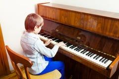 Niño divertido lindo del llittle que juega el piano Fotos de archivo libres de regalías