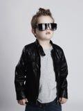 Niño divertido Niño pequeño de moda en gafas de sol niño elegante en cuero Fotografía de archivo