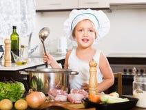 Niño divertido que cocina la sopa con las verduras Imagenes de archivo