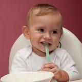 Niño divertido que come y que sostiene la cuchara Imagenes de archivo