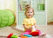Niño divertido que juega con el juguete del color interior fotos de archivo libres de regalías