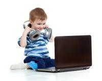 Niño divertido que juega con la computadora portátil Imagen de archivo libre de regalías