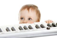 Niño divertido que se coloca detrás de piano electrónico Imagen de archivo libre de regalías