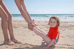 Niño divertido que se desliza por la mujer en la playa de la arena Foto de archivo libre de regalías