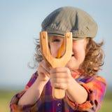 Niño divertido que tira la catapulta de madera foto de archivo