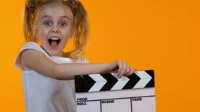 Niño divertido que usa la tablilla y sonriendo en la cámara, escuela temporaria menor almacen de metraje de vídeo