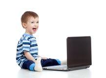 Niño divertido que usa una computadora portátil Foto de archivo