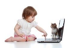 Niño divertido que usa una computadora portátil con el gatito fotografía de archivo libre de regalías