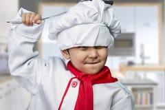 Niño divertido vestido como cocinero con una cacerola que golpea la cabeza Imágenes de archivo libres de regalías