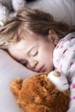 Niño dulce que duerme con el oso de peluche Imagen de archivo