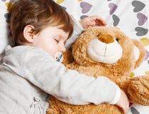 Niño dulce que duerme con el oso de peluche Fotografía de archivo libre de regalías