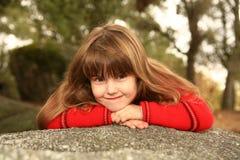Niño dulce tímido al aire libre en una roca Fotos de archivo