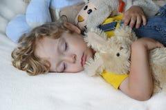 Niño durmiente con los juguetes Imagenes de archivo