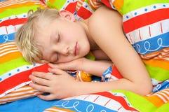 Niño durmiente en la cama Fotografía de archivo
