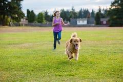 Niño el competir con de perro Fotografía de archivo