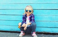 Niño elegante con la piruleta dulce en ciudad sobre azul colorido Fotos de archivo libres de regalías