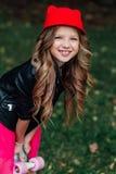 Niño elegante de la niña de la moda del retrato que presenta con el monopatín en parque de la ciudad Imágenes de archivo libres de regalías
