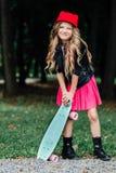 Niño elegante de la niña de la moda del retrato que presenta con el monopatín en parque de la ciudad Foto de archivo libre de regalías