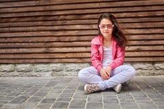 Niño elegante de la niña que lleva una chaqueta rosada del verano o del otoño, vaqueros blancos, gafas de sol Fotografía de archivo