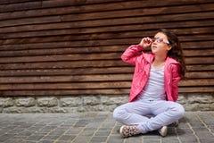 Niño elegante de la niña que lleva una chaqueta rosada del verano o del otoño, vaqueros blancos, gafas de sol Imagenes de archivo