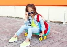 Niño elegante de la niña que se sienta en el monopatín en ciudad Foto de archivo libre de regalías