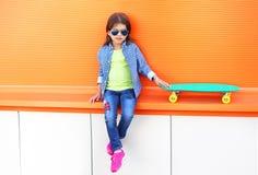 Niño elegante de la niña sentando con llevar del monopatín las gafas de sol y la camisa a cuadros Imágenes de archivo libres de regalías