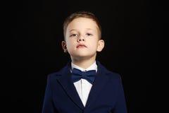niño elegante en traje sobre fondo negro Imagenes de archivo