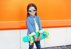 Niño elegante feliz de la niña con el monopatín sobre naranja Imagen de archivo libre de regalías