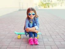 Niño elegante sonriente feliz de la niña que se sienta en el monopatín Foto de archivo