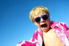 Niño emocionado de la cadera en toalla de playa y gafas de sol Foto de archivo libre de regalías