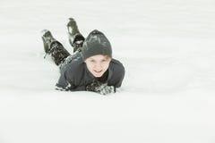 Niño emocionado que coloca en la nieve Fotos de archivo