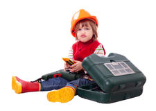 Niño emocional en el casco de protección del constructor con las herramientas Imagen de archivo