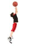 Niño enérgio del muchacho que salta con baloncesto Foto de archivo libre de regalías