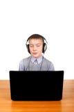 Niño en auriculares detrás del ordenador portátil Fotos de archivo libres de regalías