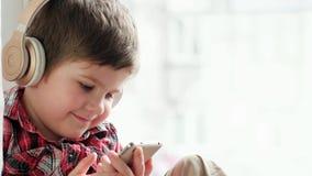 Niño en auriculares, niño que juega con smartphone y que escucha la música vía los auriculares inalámbricos almacen de video
