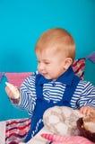 Niño en azul con las cáscaras del mar Foto de archivo libre de regalías