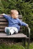 Niño en banco del jardín Imagenes de archivo