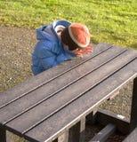 Niño en banco en parque Imagen de archivo