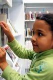 Niño en biblioteca Fotos de archivo libres de regalías