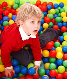 Niño en bolas coloridas. imagenes de archivo