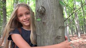 Niño en bosque, niño que juega en naturaleza, muchacha en la aventura al aire libre detrás de un árbol almacen de metraje de vídeo